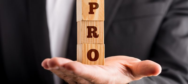 Businessman holding three wooden cubes stacked on the palm of his hand reading a PRO sign. Conceptual of professionalism and success.