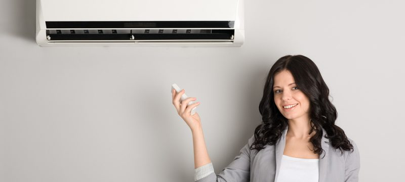 Beautiful girl holding a remote control air conditioner